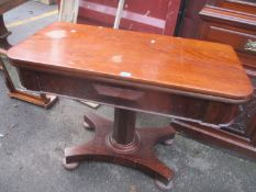 A William IV mahogany foldover dining table with an octagonal column, platform base and turned feet,