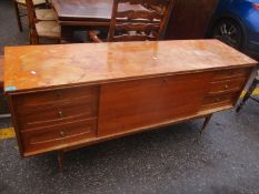 A mid 20th century teak sideboard with a fall flap flanked by six drawers, on turned tapered legs,