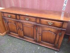 A reproduction oak Titchmarsh & Goodwin sideboard with three drawers and three cupboard doors