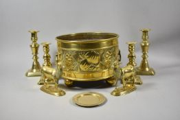 A Circular Brass Bowl with Repousse Fruit Decoration and Oval Ring Carrying Handles on Four Ball