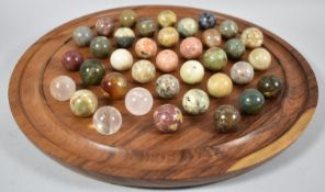 A Modern Circular Wooden Solitaire Board Complete with Collection of Stone and Crystal Marbles, many