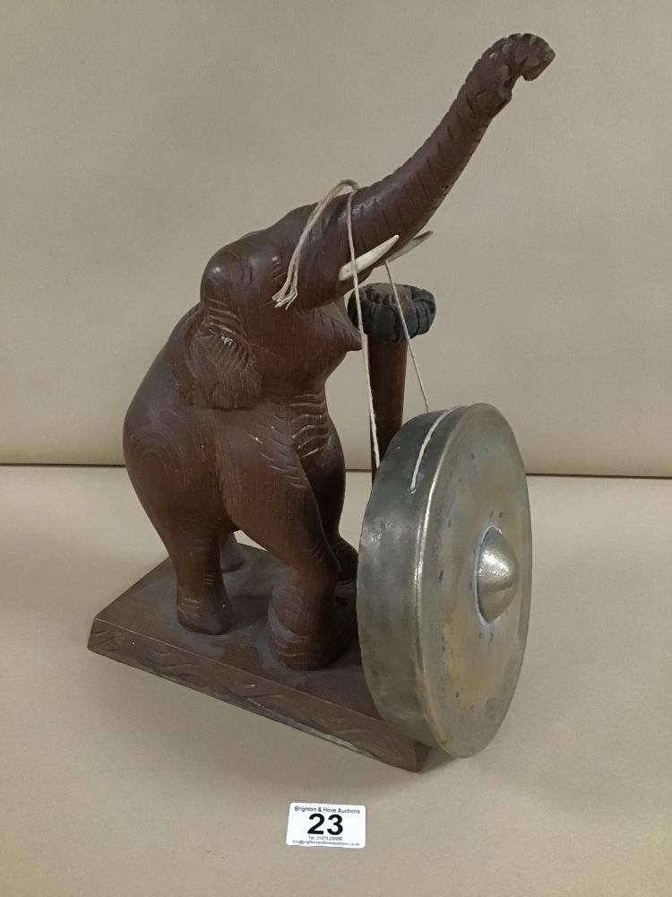 Lot 23 - AN AFRICAN CARVED WOODEN ELEPHANT GONG, ITS TUSK HOLDING THE METAL GONG, WITH CARVED BONE TUSKS,