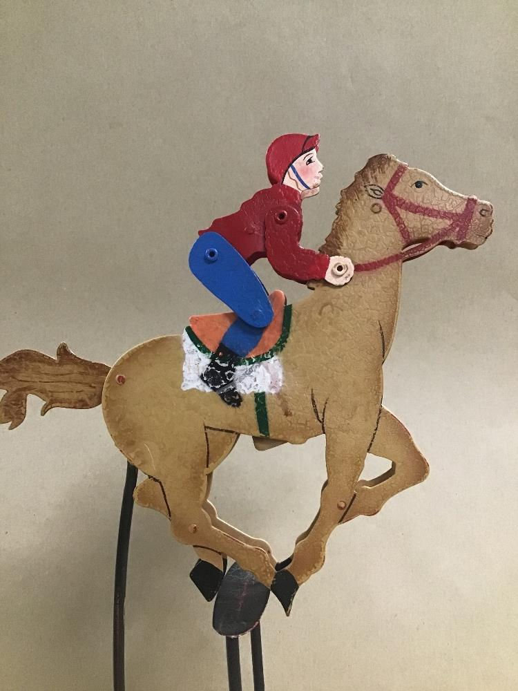 Lot 28 - A NOVELTY METAL ROCKING RACING HORSE TOY