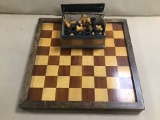 A CARVED WOODEN CHESS SET ON WOODEN BOARD