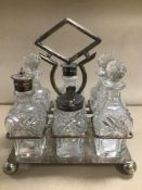 AN EARLY 20TH CENTURY SIX PIECE CUT GLASS CONDIMENT SET, MOUNTED UPON SILVER PLATE STAND BY DANIEL &