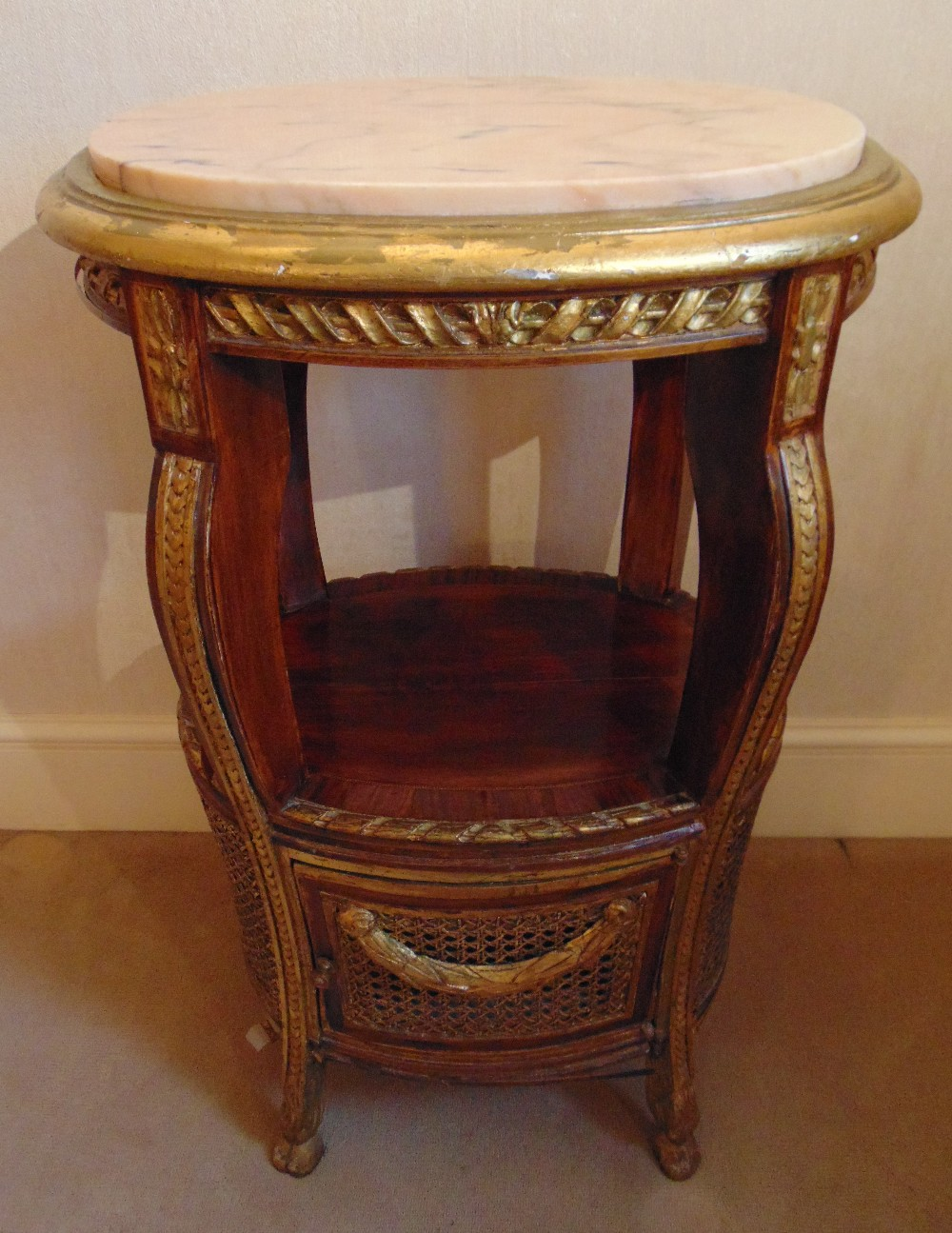Lot 16 - An oval side table with marble inset top and bergere panels to the sides, A/F