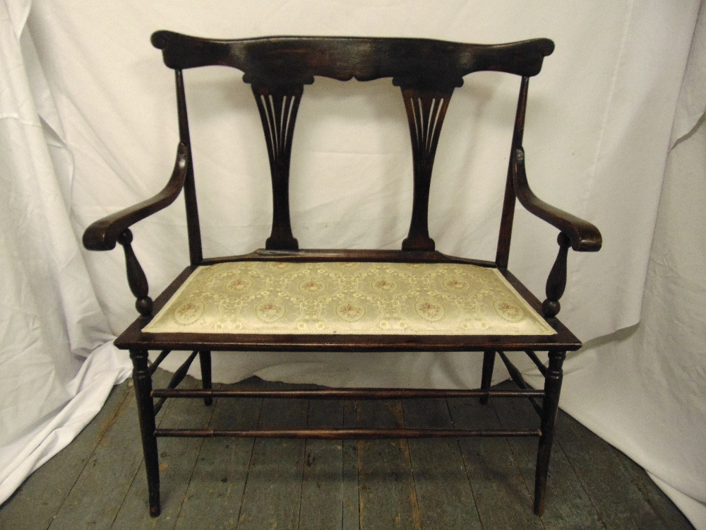 Lot 33 - A Victorian mahogany two seater settle with scrolling arms, pierced slats on four tapering