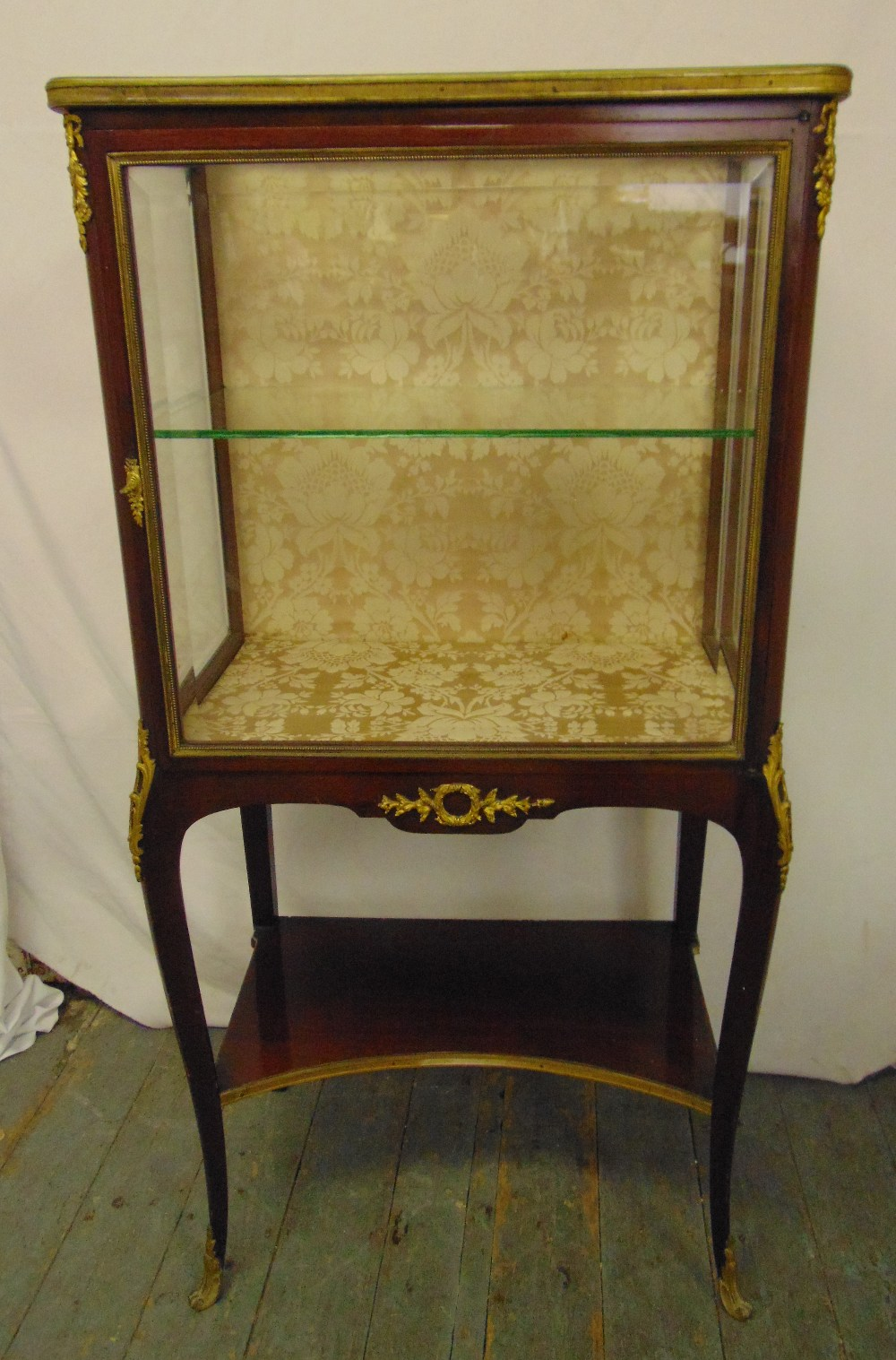 Lot 9 - A French style rectangular glazed display case with gilt metal mounts, on cabriole legs, retailed by