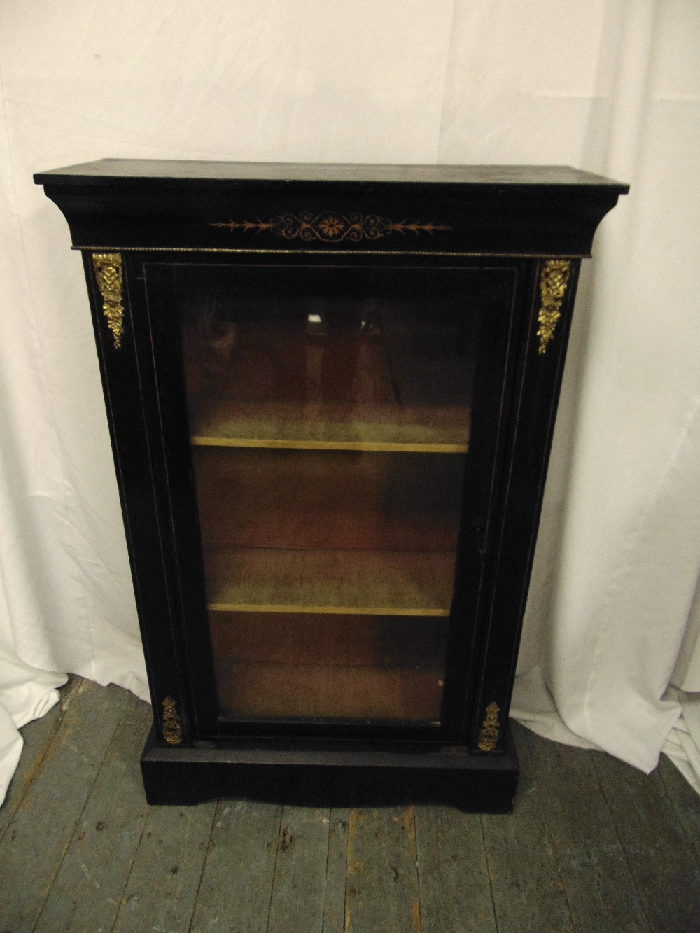 Lot 10 - A rectangular ebonised and glazed display cabinet on raised rectangular plinth with brass mounts