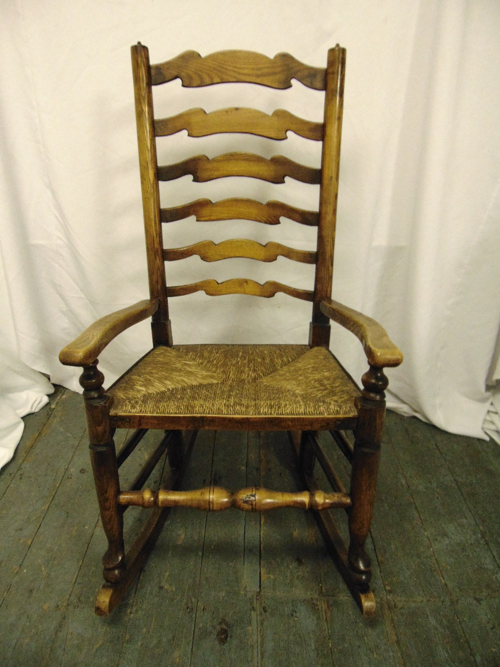 Lot 32 - An oak rocking chair with scrolling arms and rush seat