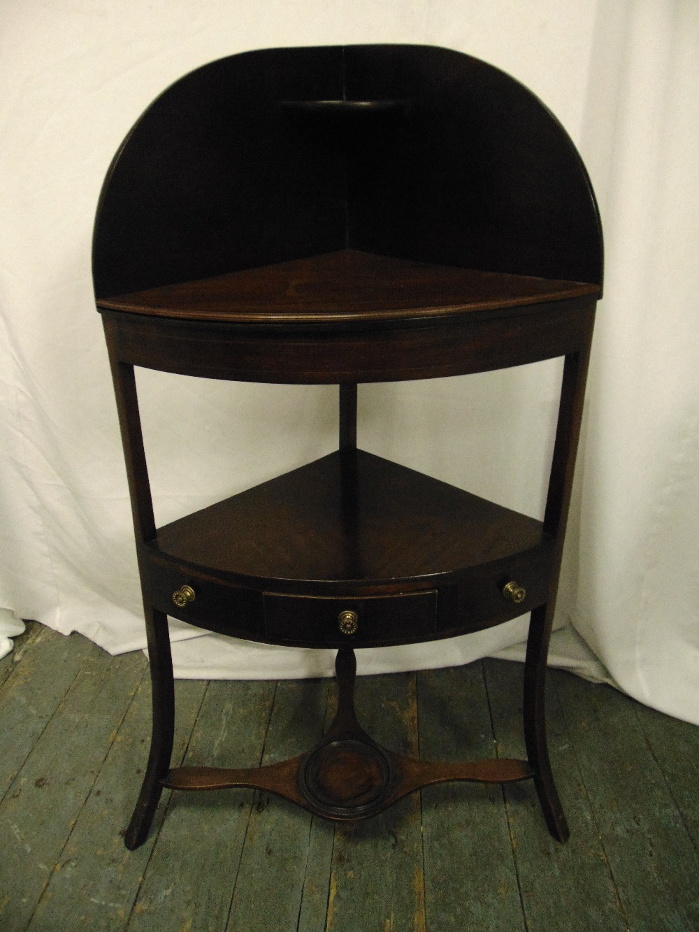 Lot 13 - A Sheraton style mahogany corner stand on three outswept supports and a single drawer with turned