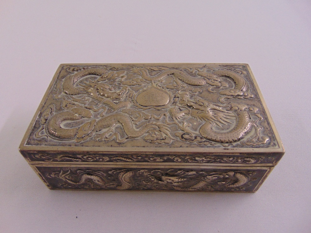 Lot 448 - A Chinese white metal rectangular casket profusely chased with dragons to the sides and hinged