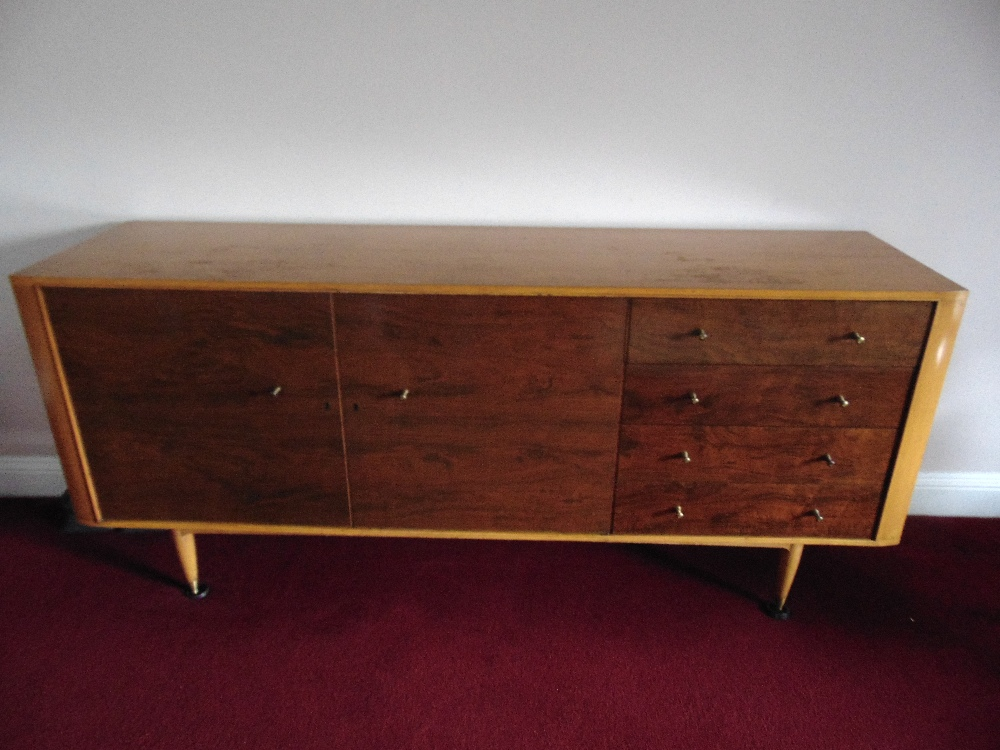 Lot 6 - A rectangular yew wood sideboard with four drawers and two cupboards on four tapering cylindrical