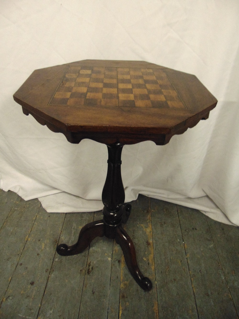 Lot 18 - A Victorian mahogany octagonal games table the top inlaid with a chequer board, on a baluster stem