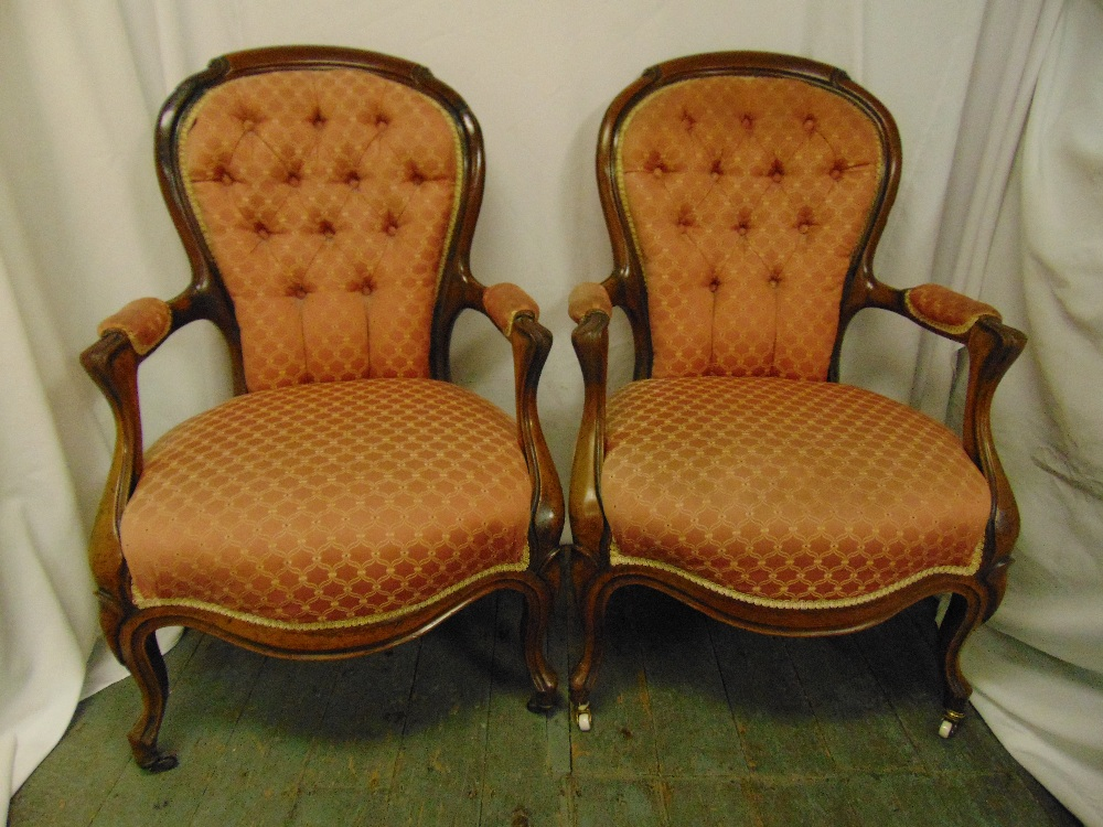 Lot 21 - A pair of Victorian mahogany upholstered armchairs on cabriole legs