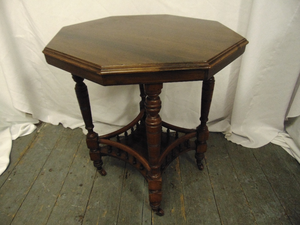 Lot 14 - An Edwardian octagonal mahogany gallery side table on turned legs and castors