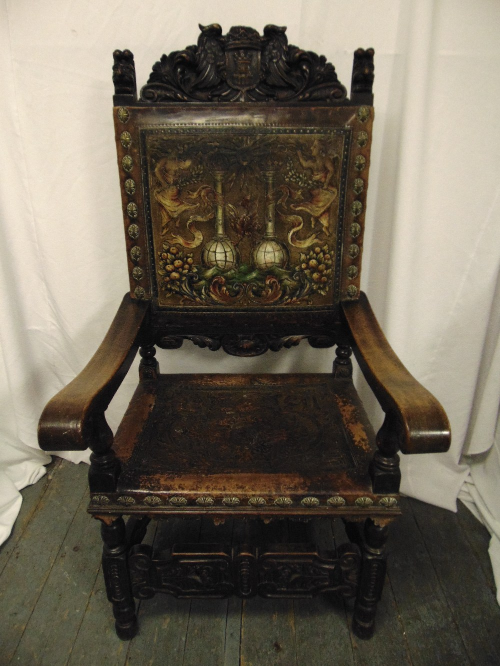 Lot 20 - An antique Spanish walnut throne, heavily carved and with embossed coloured seat and back,