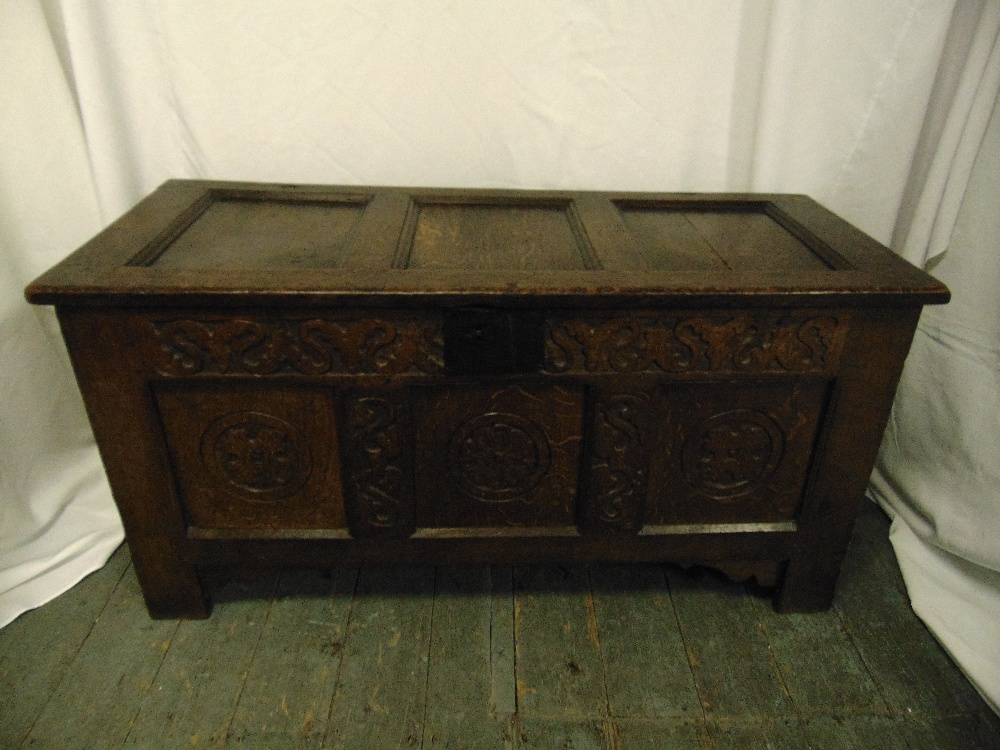 Lot 34 - An early rectangular oak coffer with carved side panels, hinged cover and bracket feet