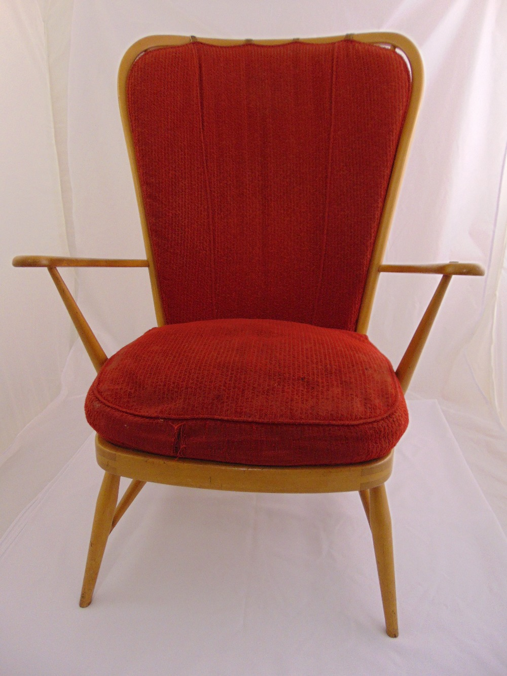 Lot 17 - A mid 20th century Ercol elm armchair with upholstered back and seat on four tapering tubular legs