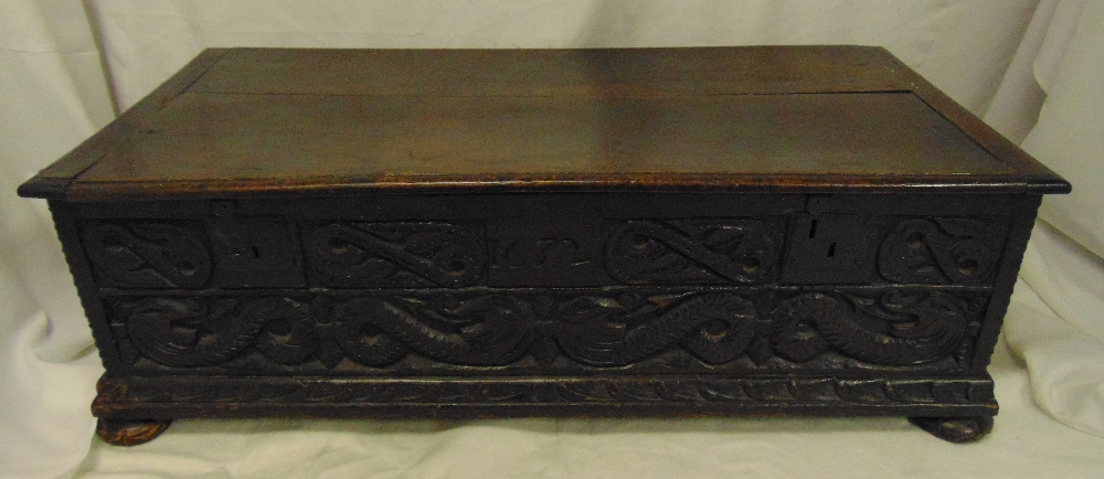 Lot 11 - A rectangular oak blanket box with carved 17th century side panels hinged cover on four bun feet