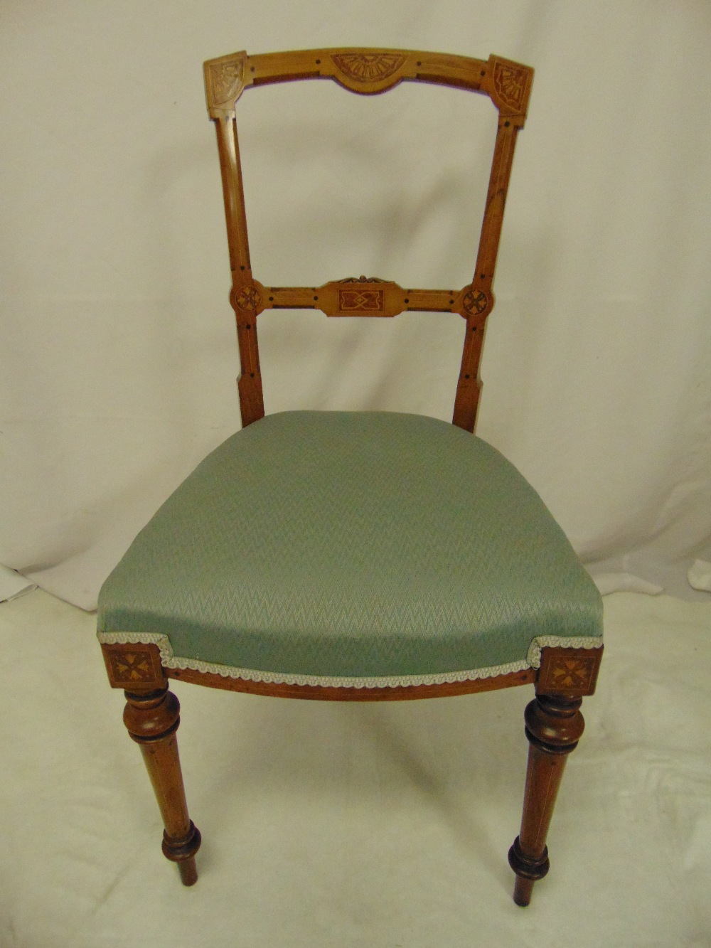 Lot 21 - A mahogany inlaid occasional chair on four turned tubular legs