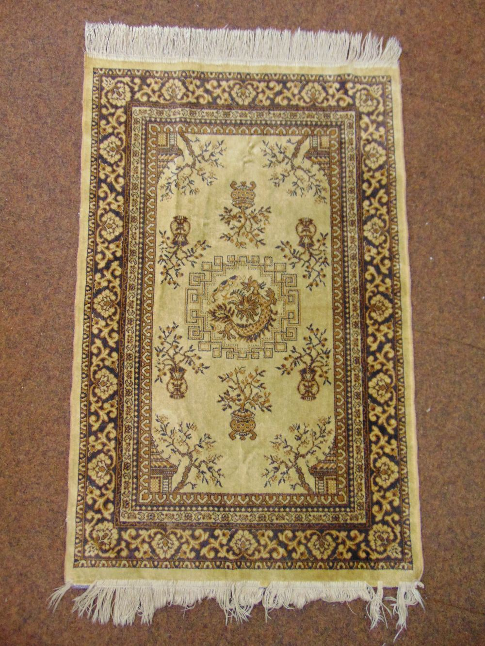 Lot 25 - A silk prayer rug with geometric borders and organic repeating motifs to the centre, 108 x 68.5cm