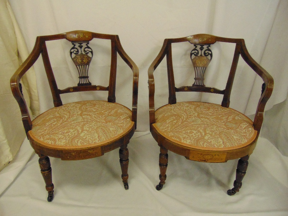 Lot 20 - A pair of Edwardian mahogany inlaid upholstered armchairs on four turned tubular legs