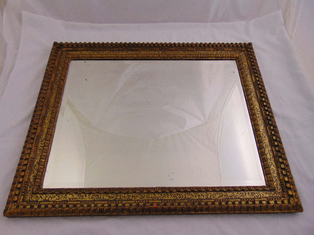 Lot 26 - A rectangular carved gilded wooden wall mirror with stylised leaf and scroll inner border, 77 x