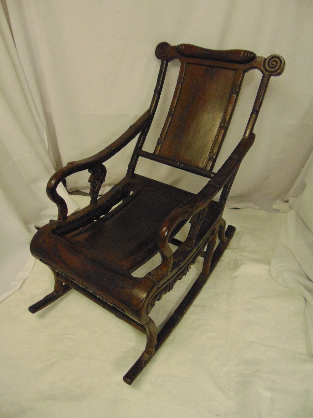 Chinese hardwood rocking or moon chair of simulated bamboo form with scrolling arms and runners