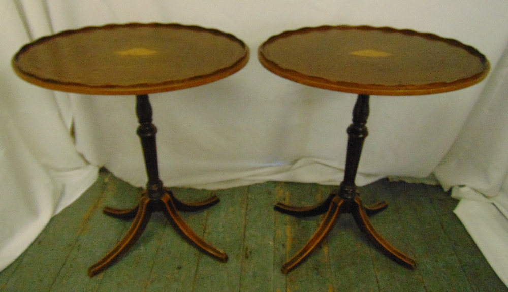 Lot 12 - A pair of Edwardian oval side tables inset with satinwood stringing and decoration on four
