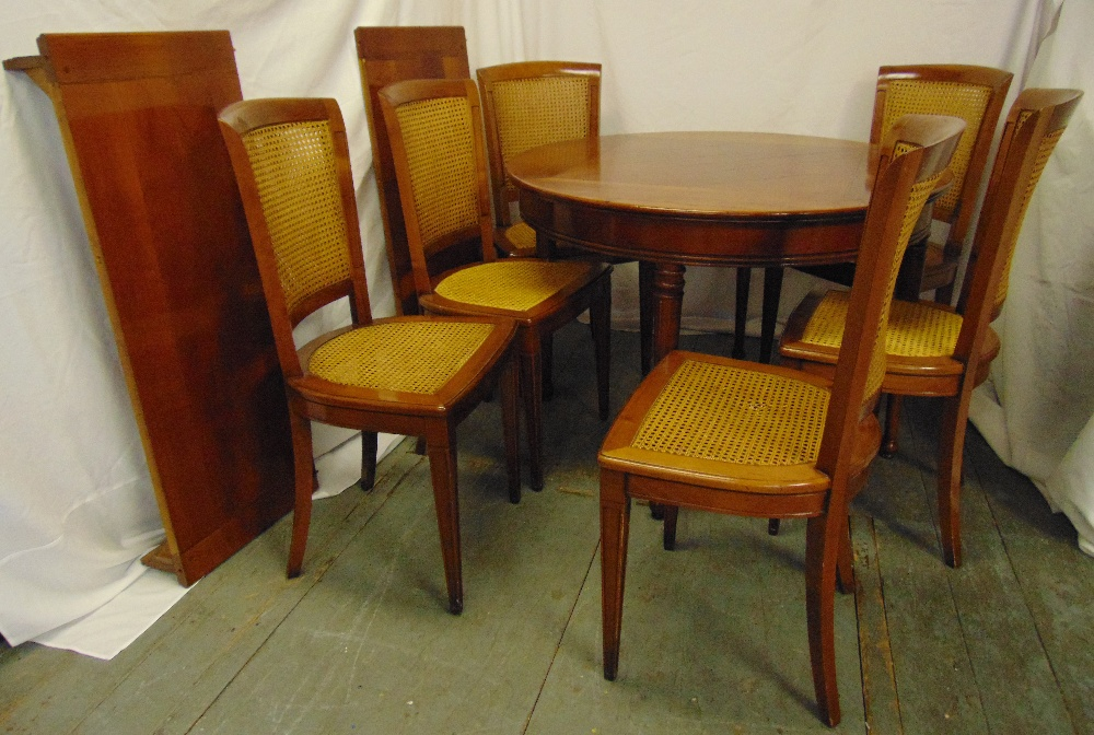Lot 7 - A mahogany circular dining table with two drop in leaves and six matching caned dining chairs, 78