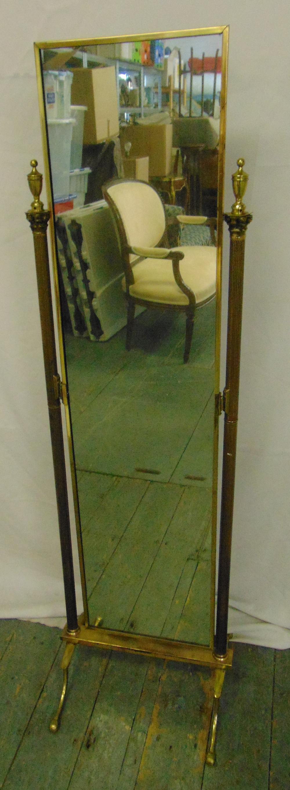 Lot 26 - A gilded metal rectangular cheval mirror with urn finials to the sides on four scroll supports,