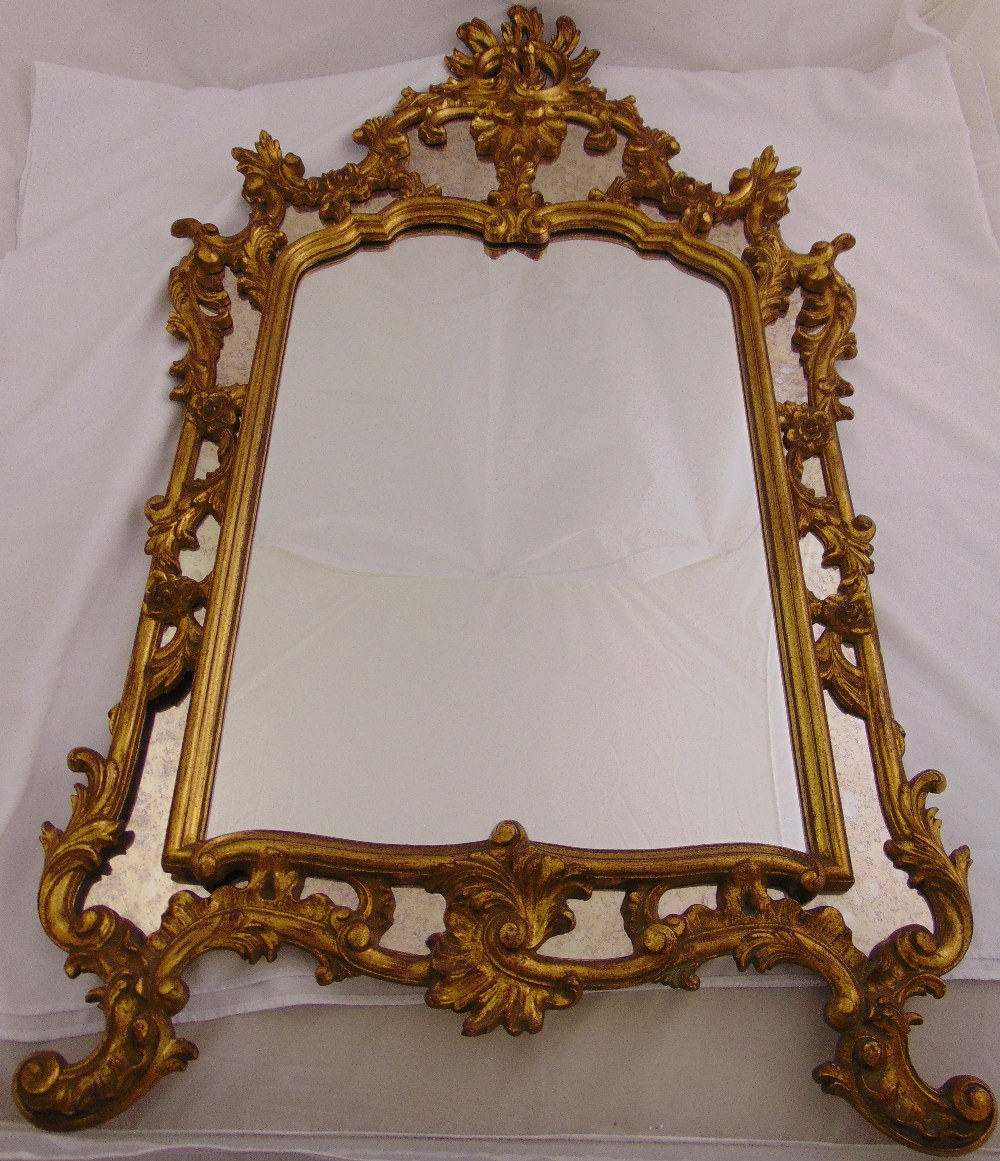 Lot 27 - A gilded wooden Rococo style hall mirror of pierced rectangular form, 137 x 83cm