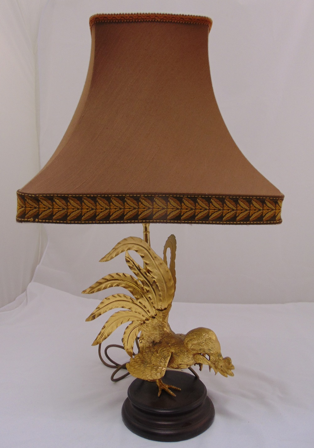 Lot 37 - A gilded metal table lamp in the form of a cockerel on circular wooden base, to include shade,