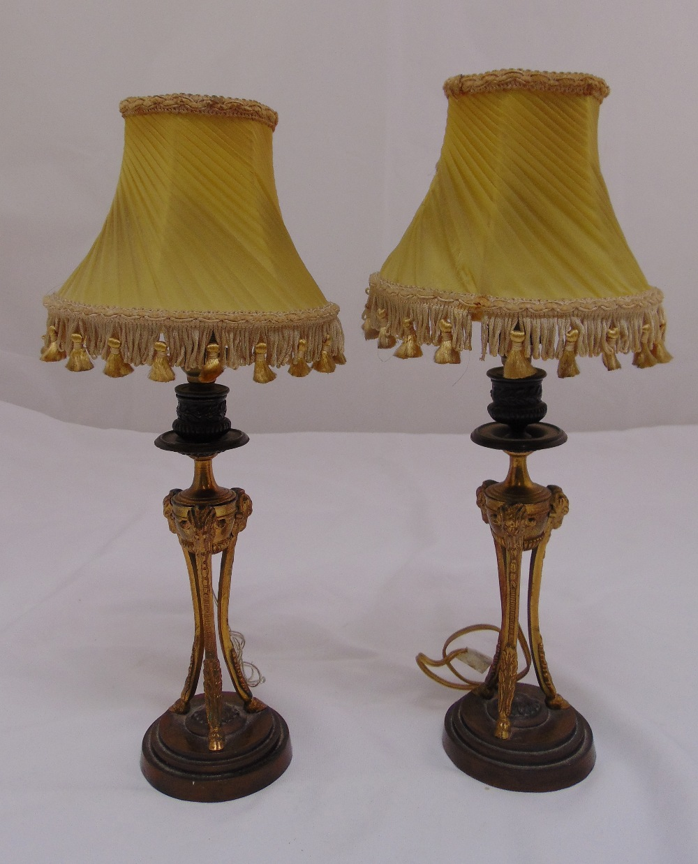 Lot 33 - A pair of gilded metal table lamp stands on raised circular bases with shades, 38cm (h)