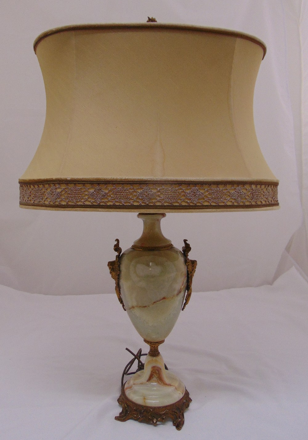 Lot 38 - An onyx baluster form table lamp with gilt metal mounts on circular base, to include shade, 78cm (