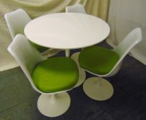 A mid 20th century circular white Tulip table and four matching chairs with detachable cushions,
