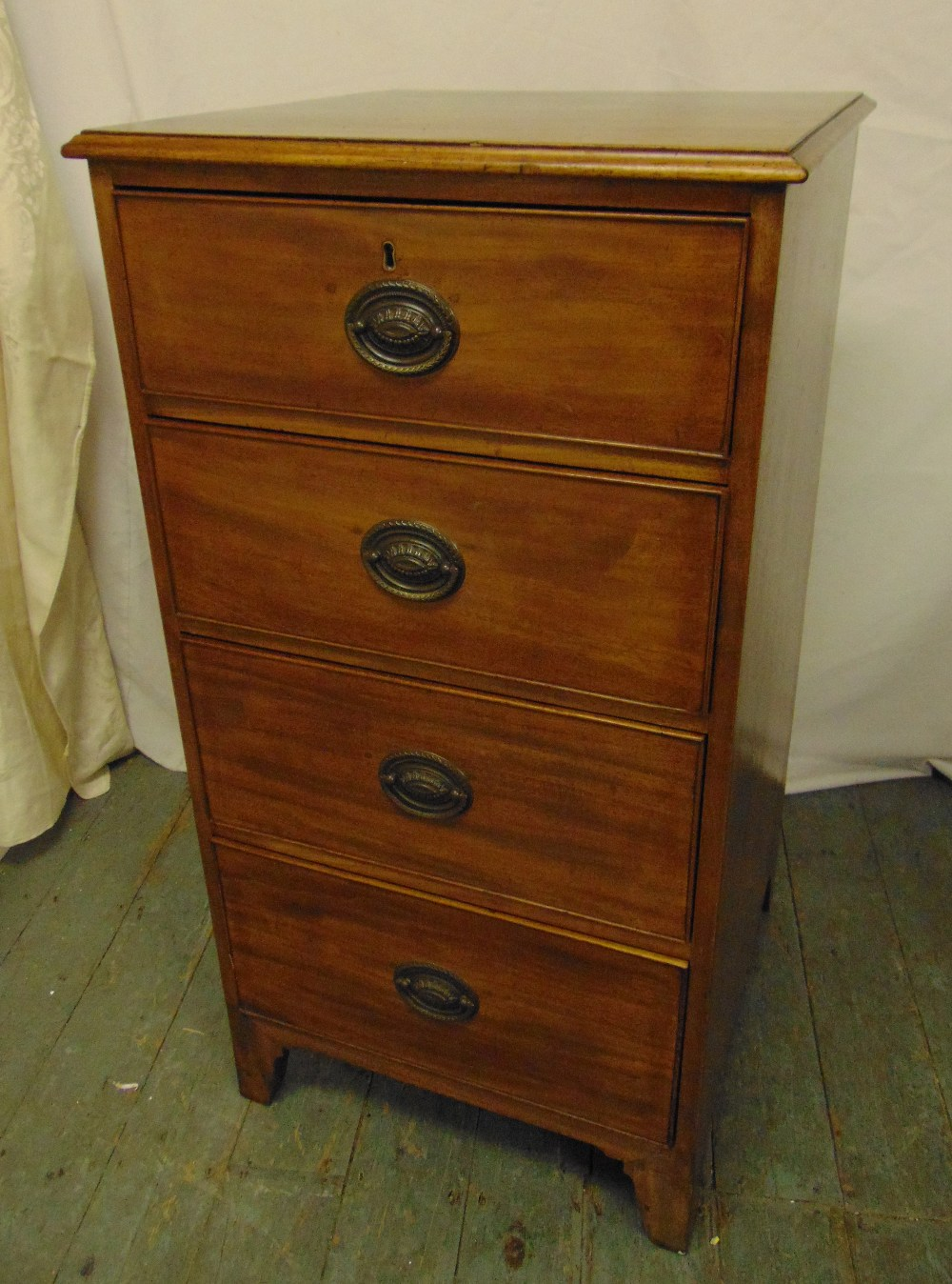 Lot 9 - A rectangular mahogany chest of four drawers with brass swing handles on bracket feet, 107 x 56.5
