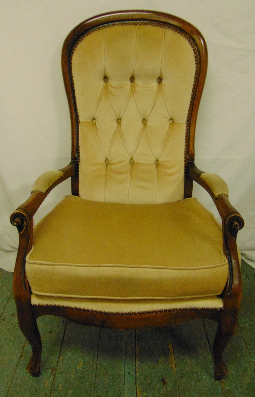 Lot 36 - A mahogany button back armchair with scrolling arms and legs