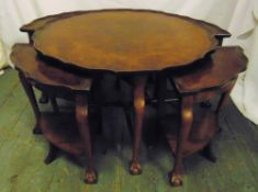 A circular walnut coffee table with piecrust border, scroll legs, ball and claw feet with four
