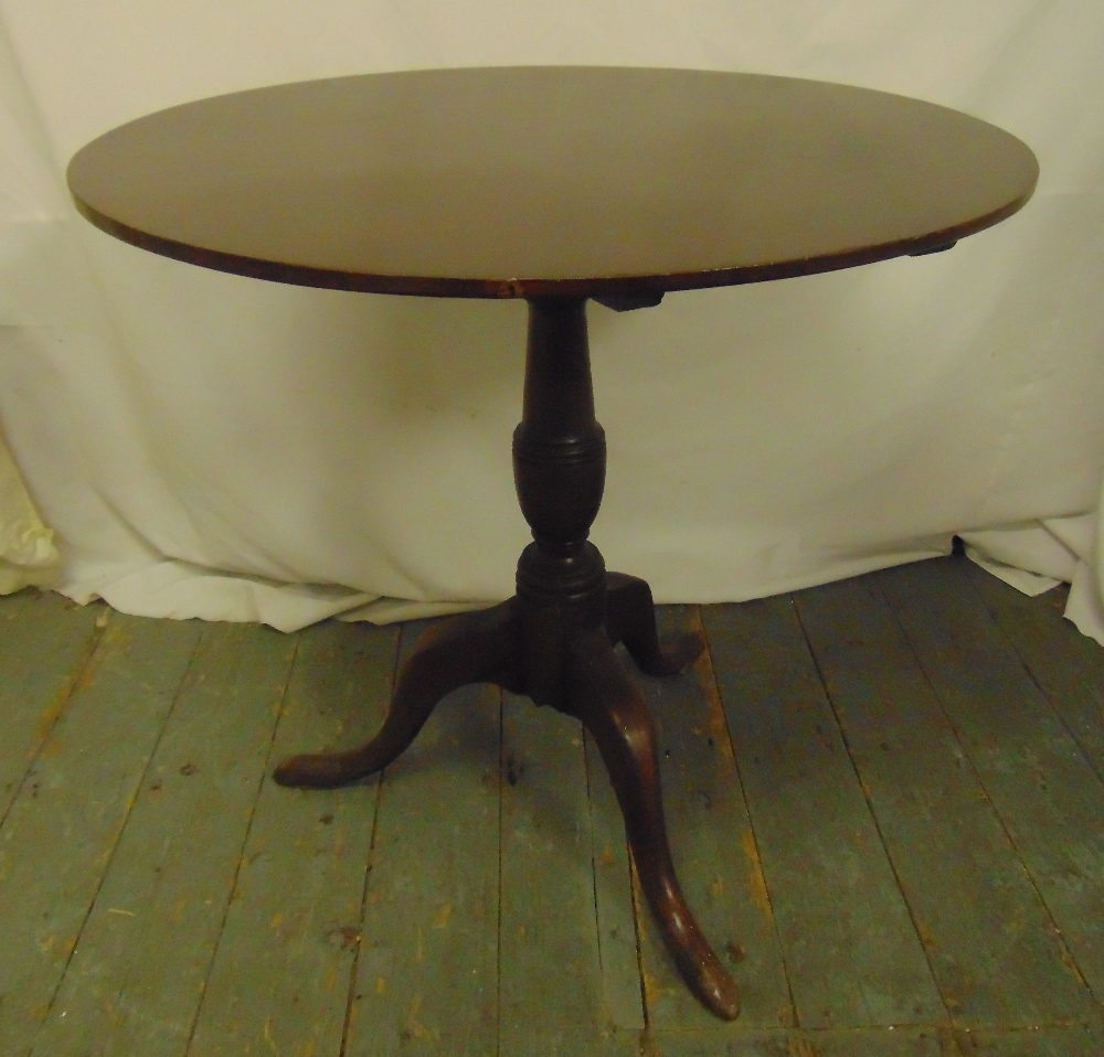 Lot 17 - A mahogany circular tilt top occasional table on three outswept legs, 70 x 74cm