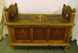 A late 19th century ottoman of rectangular form with two hinged seats, panelled sides on four