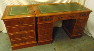 A rectangular yew wood desk with tooled leather top, nine drawers with brass swing handles