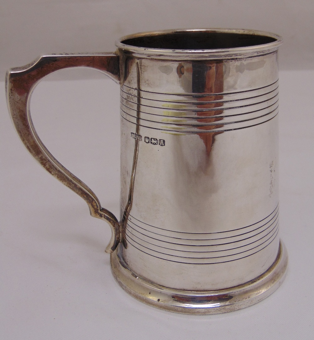 Lot 373 - A silver mug tapering cylindrical, the sides engraved with bands with pierced scroll handle on rim
