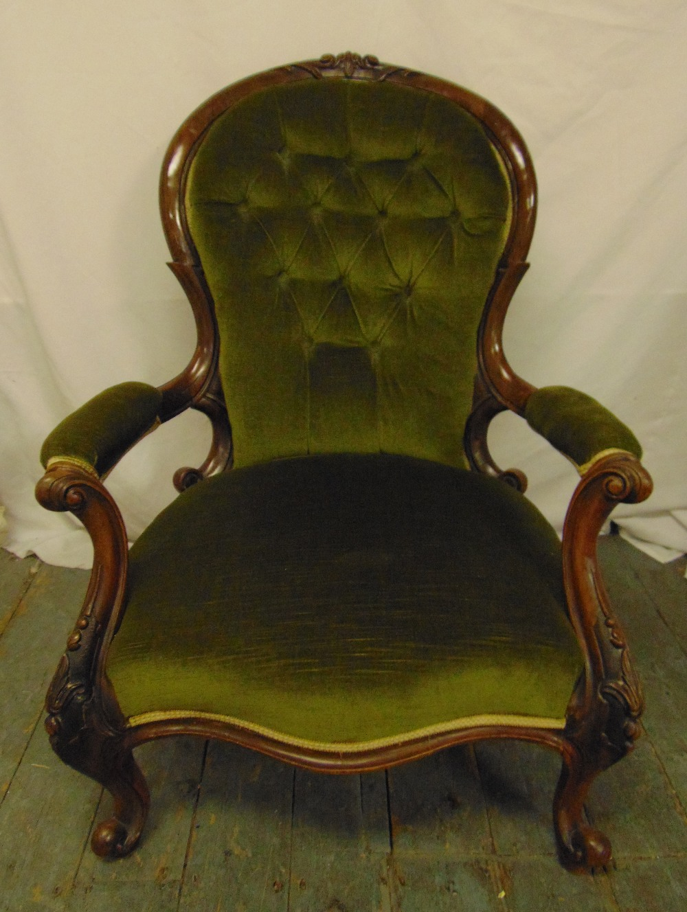 Lot 31 - A Victorian mahogany button back upholstered armchair on carved cabriole legs, 94 x 71 x 74cm