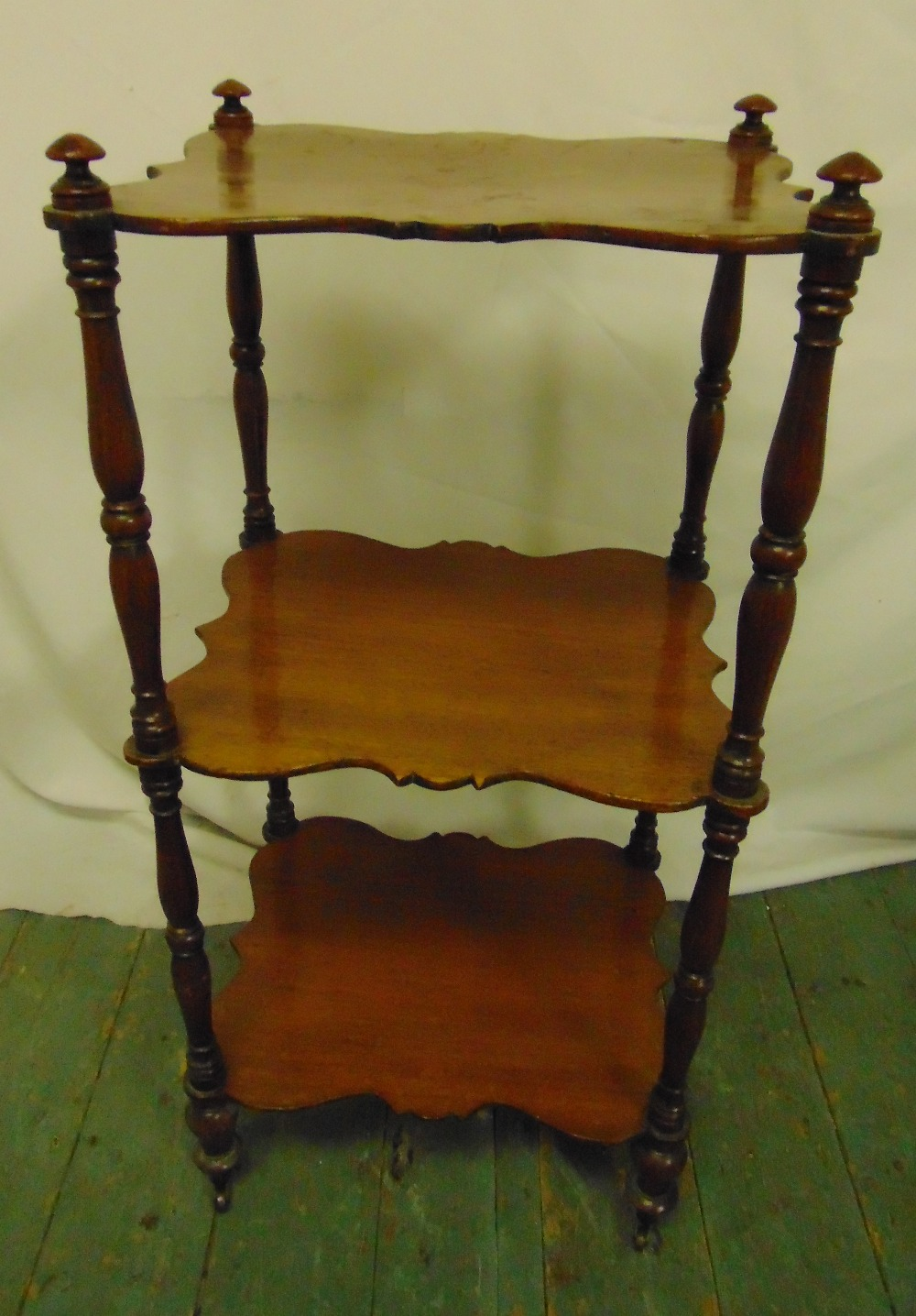 Lot 22 - A mahogany shaped rectangular three tier whatnot with four turned cylindrical supports, 82 x 38.5