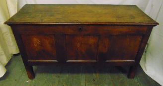A rectangular oak coffer of panelled form with hinged cover on four rectangular legs, 65.5 x 112.5 x
