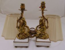 A pair of late 19th century continental ormolu putti supporting light fittings on square marble