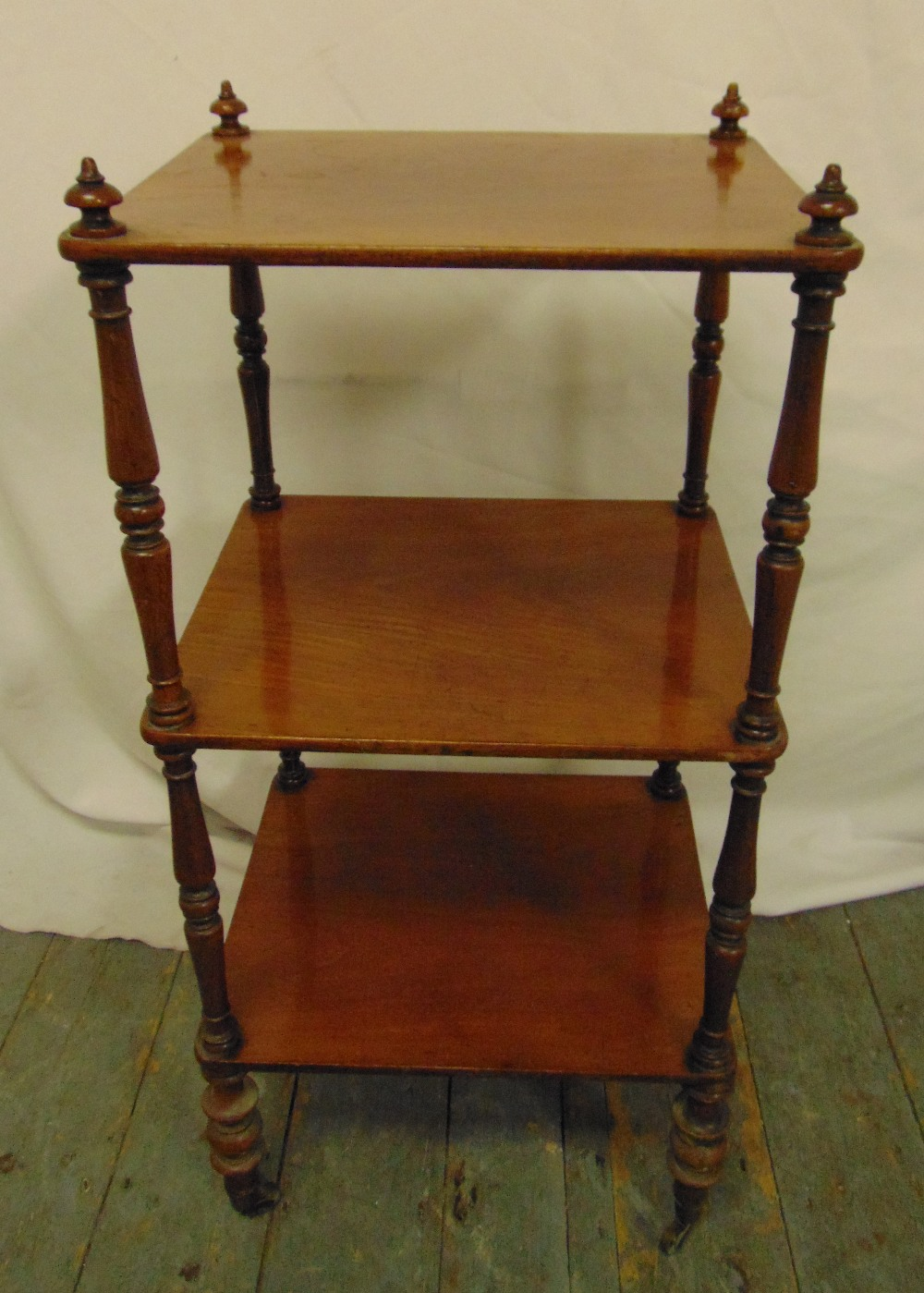 Lot 21 - A mahogany rectangular three tier whatnot, with four turned cylindrical supports, 80 x 38 x 33cm