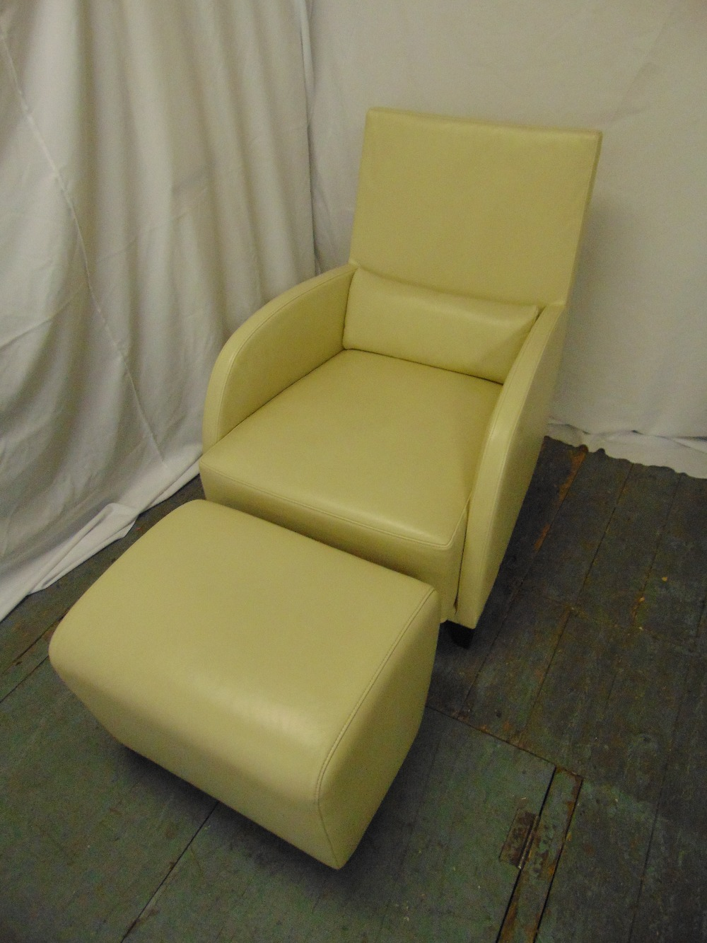 Lot 9 - A cream leather occasional chair and matching footstool by Ligne Roset